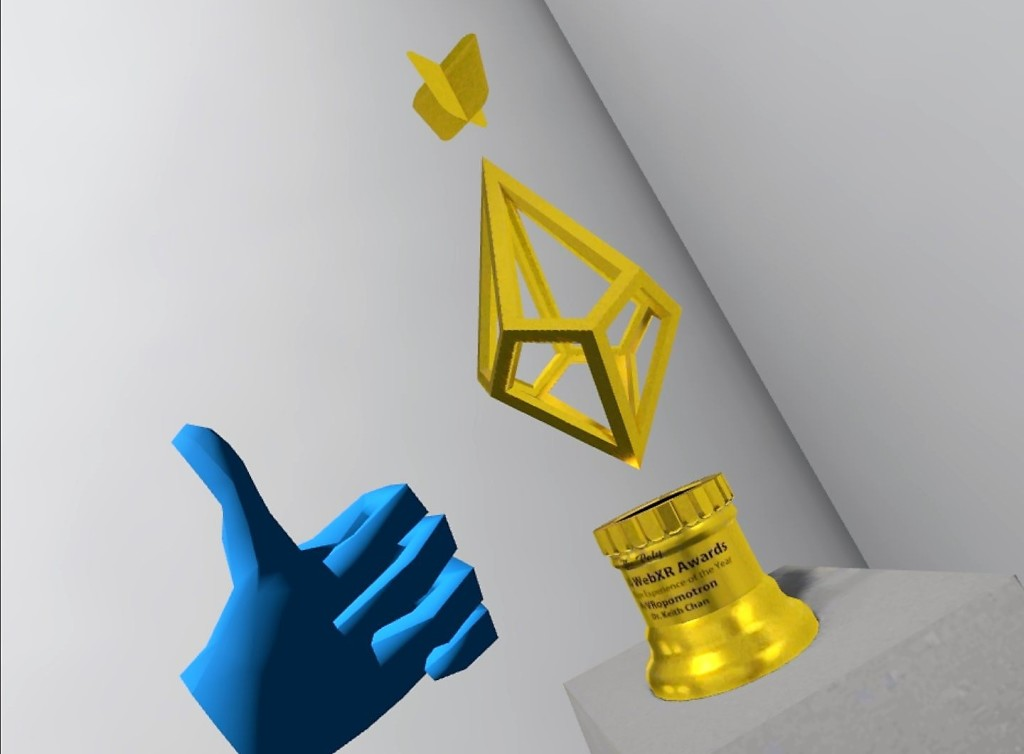 Gold model of the hovering WebXR trophy on a gray pedestal, with a thumbs-up hand next to it